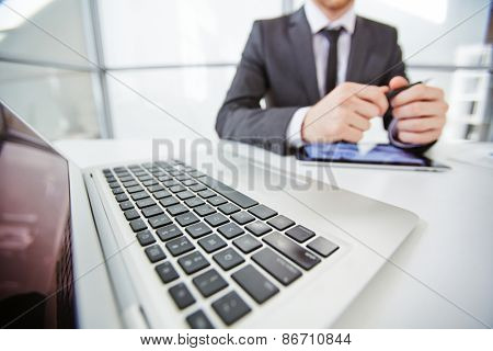 Laptop keyboard and businessman with touchpad on background
