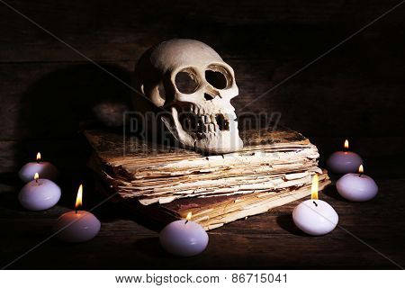 Still life with human skull, retro book and candlelight in dark on wooden table, closeup
