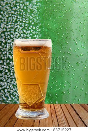 Beer Glass Against Ice Crystals And Drips Green Background.