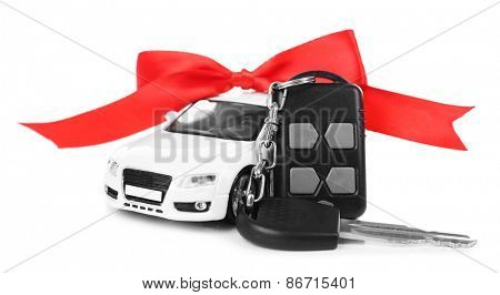 Keys with red bow near car as present isolated on white