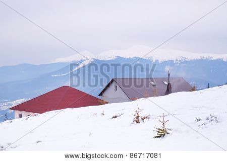 Buildings over snowy mountains in wintertime