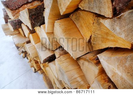 Firewood in snow outdoors, closeup