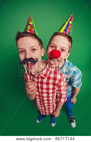 Hilarious twins with clown nose and moustache during foolâ??s day celebration