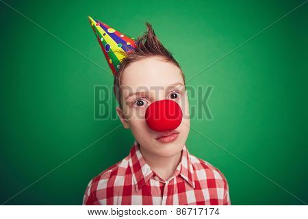 Cute boy with birthday cap and red nose looking at camera