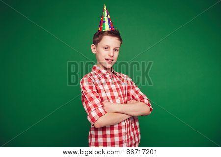Happy kid with birthday cap looking at camera