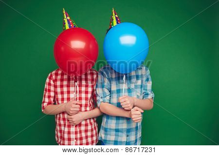 Two boys hiding behind red and blue balloons