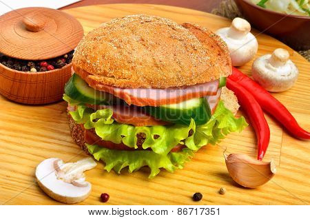 Tasty Hamburger  Filled With Ham, Mushrooms, Cucumber And Fresh Salad,pepper Pot, Chili Pepper On Cu