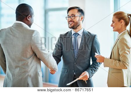 Happy businessmen handshaking after striking deal