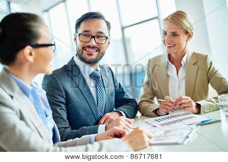 Happy businessmen and two pretty employees communicating at meeting