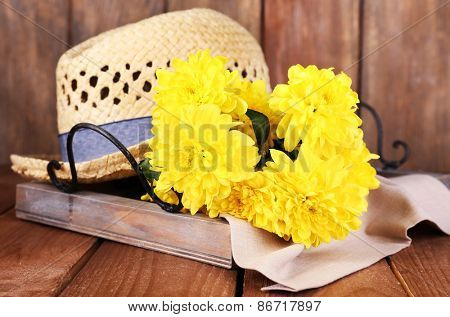 Hat with flowers on wooden background