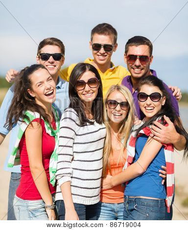 summer holidays, vacation, tourism, travel and people concept - group of happy friends having fun and hugging on beach