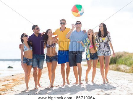 summer holidays, vacation, tourism, travel and people concept - group of happy friends playing with inflatable ball walking along beach