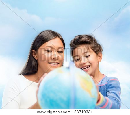 family, children, education, geography and people concept - happy mother and daughter with globe over blue sky background