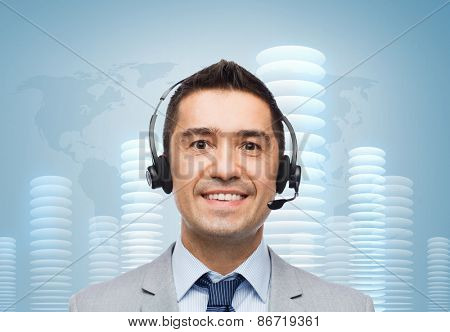business, people, technology and financial concept - smiling businessman in headset over blue background with world map and bit coin towers