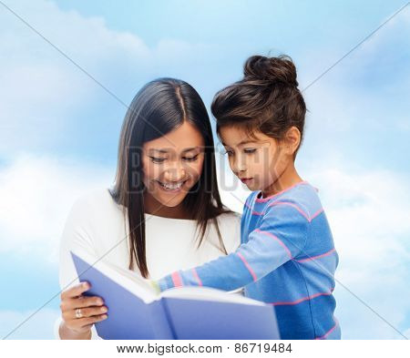 family, children, education, school and happy people concept - happy mother and daughter reading book over blue sky background