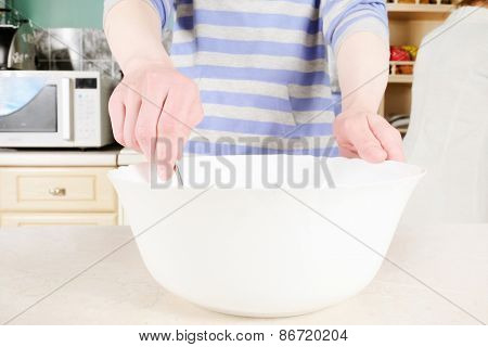 Woman cooking in the kitchen with white bowls