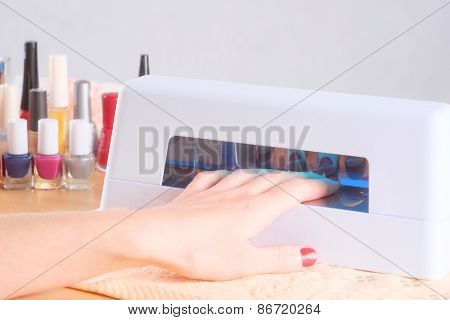 Closeup of drying finger nails under UV lamp