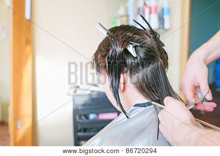 Hairdresser making a haircut for a brunette women