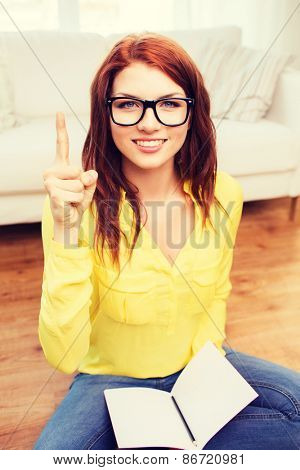 home, education, gesture and people concept - smiling teenage girl sitting on the floor with workbook at home