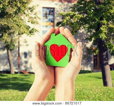 charity, real estate and family home concept - closeup picture of female hands holding green paper house with red heart