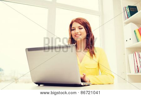 business, office, school and education concept - smiling businesswoman with laptop computer in office