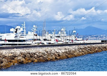 Luxury yachts anchored by a rocky pier in marina in South of France on a sunny summer day