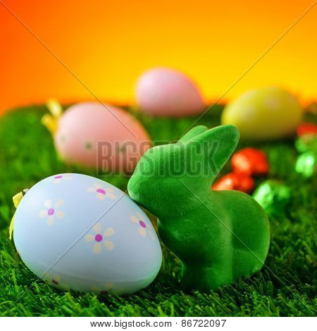 closeup of a green easter rabbit and a blue flower-patterned easter eggs on the grass with some colorful decorated eggs in the background