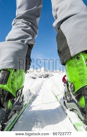 Close Up Of Skier's Boots And Skis From Ground Level.