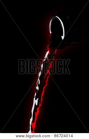 Red wine pouring from bottle isolated on black background