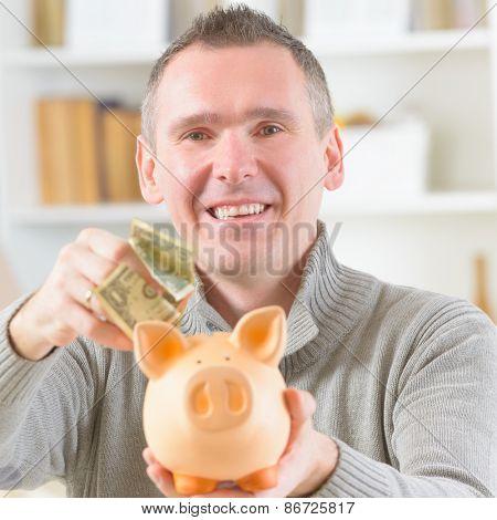 Man putting money in piggybank, concept of saving