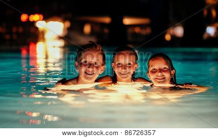 Three Kids In Illuminated Pool