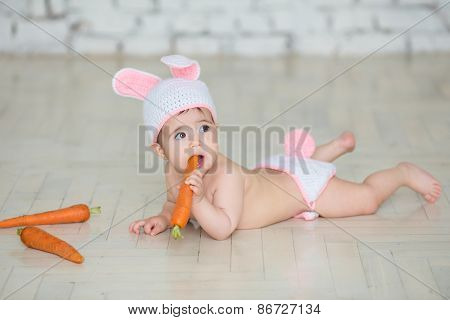 Portrait Of A Cute Baby Dressed In Bunny Ears With Carrot