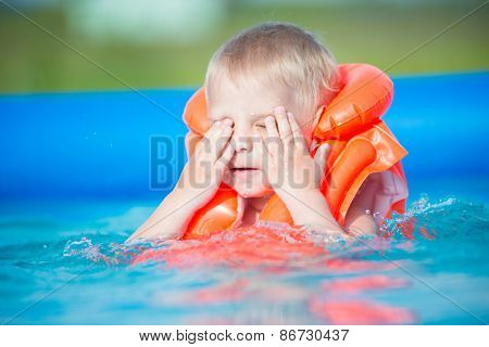 Pretty little boy in swimming pool
