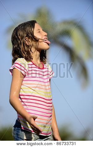 Happy smiling little girl outdoor in a sunny day enjoying the light rain.
