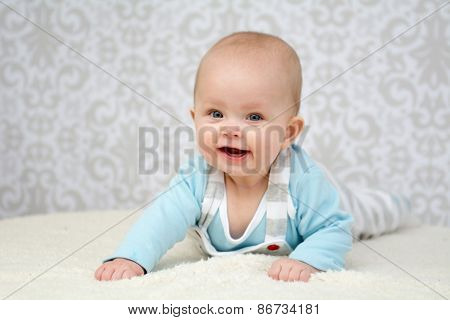Cute Little Baby With Blue Eyes Giving Big Smile Into The Camera