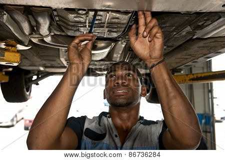 Mechanic Checking Under Vehicle