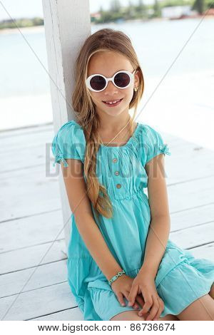 Preteen child wearing aqua blue fashion clothes resting at the beach in summer