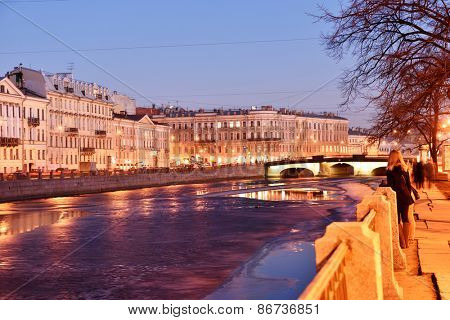 ST. PETERSBURG, RUSSIA - MARCH 16, 2015: People resing on the embankment of river Fontanka in evening. There is at least 93 rivers and canals in the city