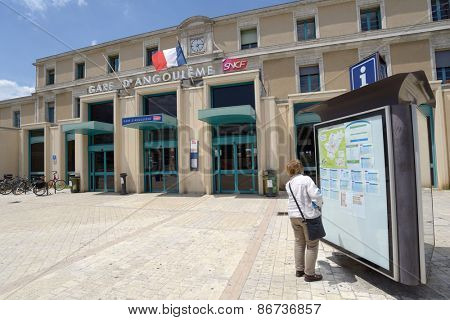 ANGOULEME, FRANCE - JUNE 26, 2013: Woman looking at timetables in front of train station. The station building is part of the former College Royal de la Marine