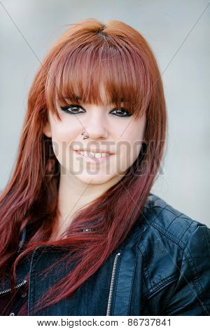 Rebellious teenager girl with red hair smiling