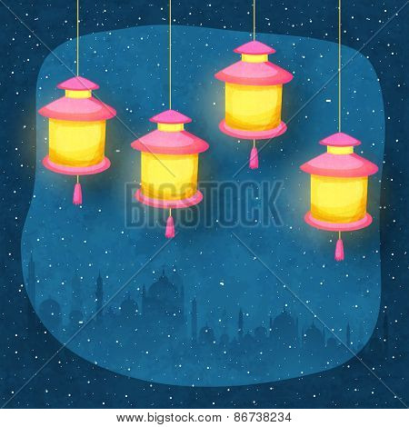 Illuminated arabic lanterns hanging on blue night background with silhouettes of mosque, concept for Muslim community holy month of prayers, Ramadan Mubarak.