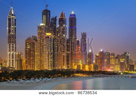 DUBAI, UAE - 2 APRIL 2014: Skyscrapers of Dubai Marina at night, UAE. Dubai Marina is a district in Dubai with artificial canal city who accommodates more than 120,000 people at Persian Gulf.