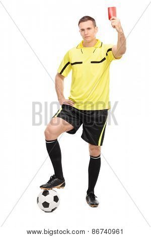 Full length portrait of a strict football referee standing over a ball and showing a red card isolated on white background