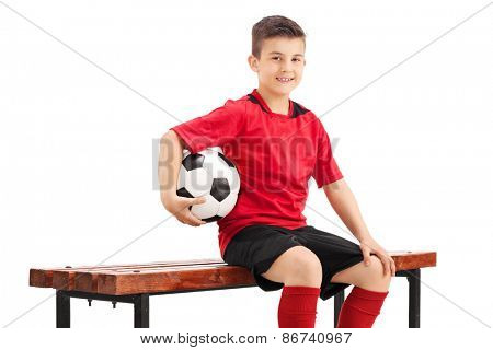 Proud junior football player posing seated on a wooden bench and holding a football in his hand isolated on white background