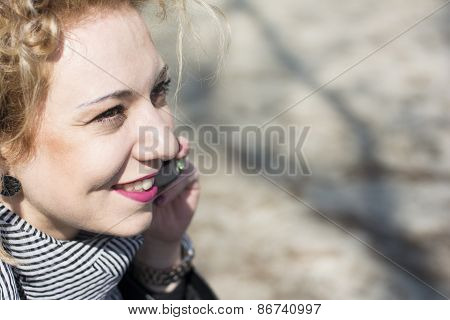 Young Curly Blond Woman Talking On The Phone In Outdoors