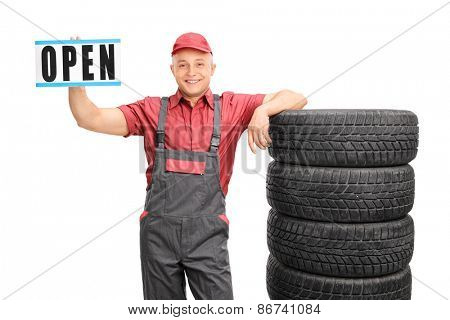 Cheerful mechanic holding an open sign and standing next to a stack of tires isolated on white background