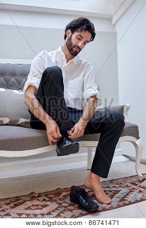 professional man getting ready for work putting smart shoes on and tying shoelaces at home