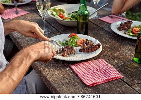man eating healthy fresh salad at outdoor barbecue garden party gathering
