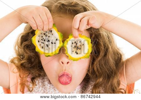 Cute little preschooler girl holding pitahaya slices in front of her eyes