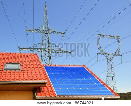 Solar panel on the roof of the house in the background high voltage pylons